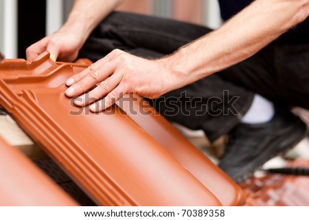 Roofing - construction worker standing on a roof covering it with tiles - stock photo