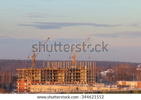 Roofs of residential buildings in snow and cranes at sunny winter evening in Perm, Russia - stock photo