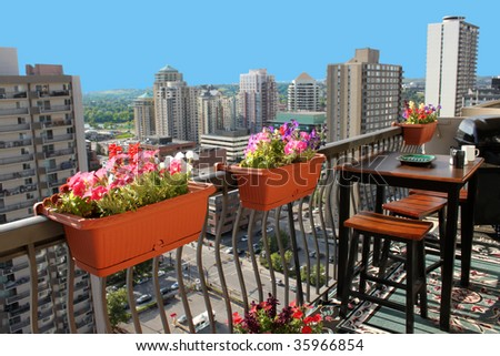 Rooftop patio with table and stool chairs, colorful flower baskets along a balcony railing with Calgary building skyline in the background - stock photo