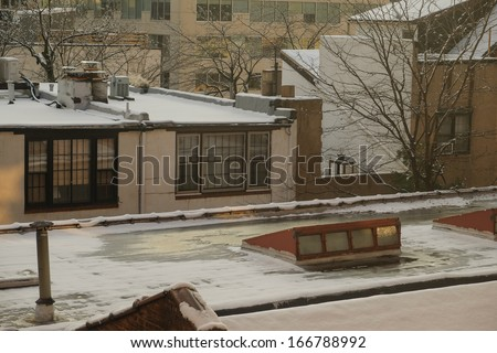 Rooftop skylights in a light snow falling - stock photo
