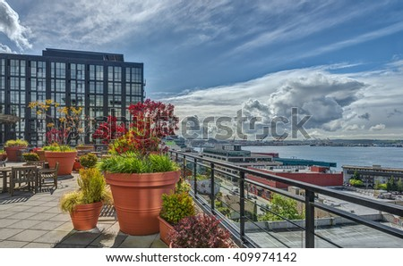 Rooftop Terrace with Flower Pots and Views of Puget Sound, Seattle Great Wheel, and Ferry Terminal - stock photo