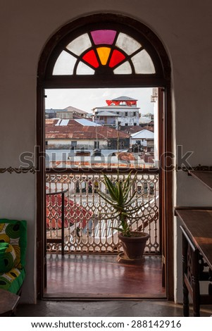 rooftop view over stonetown zanzibar looking through a stainer glass doorway arch. - stock photo