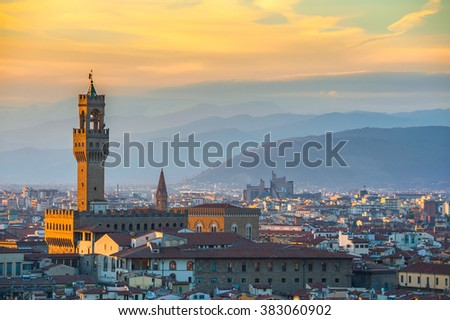 Rooftops of Florence in last light with pale orange clouds and mauve distant hills