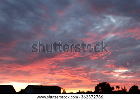 Rooftops silhouette, Ominous Red and Grey Clouds on a  fiery sunset wide. - stock photo