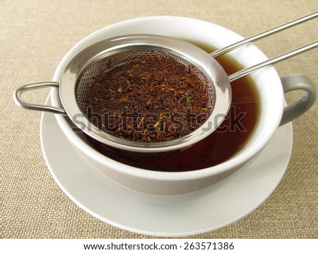 Rooibos tea in tea strainer - stock photo