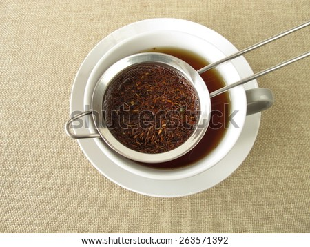 Rooibos tea in tea strainer - stock photo
