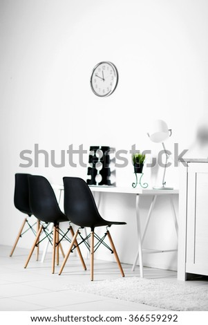 Room interior with clock, chairs and table on white wall background - stock photo