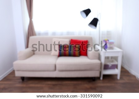 Room interior with comfortable sofa and colourful pillows, blurred