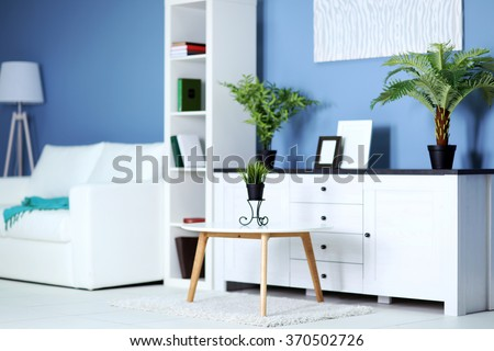 Room interior with commode, bookcase, table and sofa on blue wall background - stock photo
