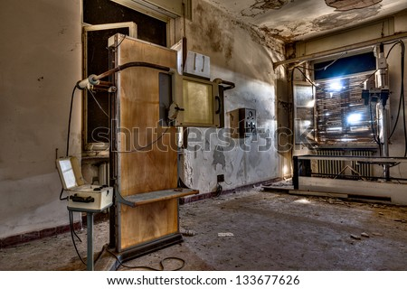 room of an abandoned hospital with old radiological equipment - desolate x-ray room in ruins - stock photo