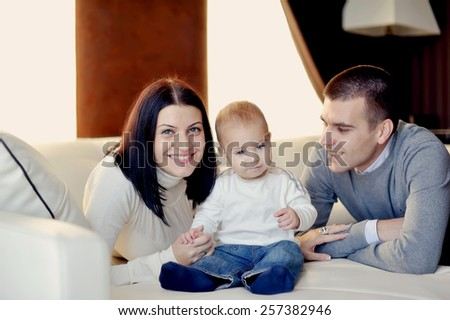 room on a white bed happy young family playing with his young son - stock photo