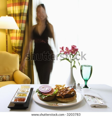 Room service cheeseburger meal with flowers and Taiwanese mid adult woman in background. - stock photo