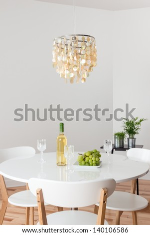 Room with decorative chandelier, white round table and plants. - stock photo