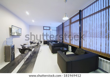 Room with modern interior with black leather sofas and tables - stock photo