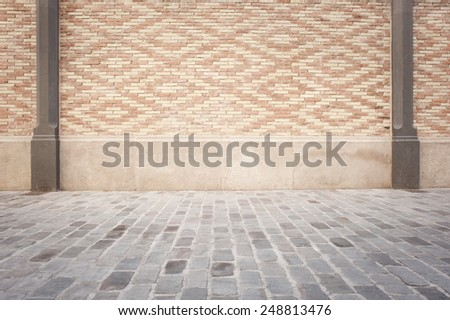 room with white bricks wall and cobblestone floor - stock photo