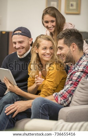 roommates choosing tv program on digital tablet
