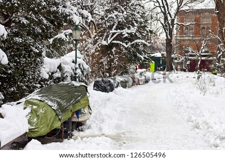 Roost of some homeless people on the bench of a public park in Vienna during a damn cold winter. - stock photo
