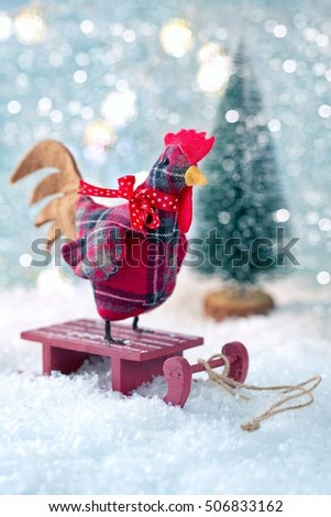 Rooster is a symbol of 2017. Decoration toy on a Christmas background. Christmas card.