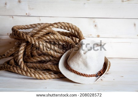 rope and women's straw hat in cowboy style on the wooden background - stock photo