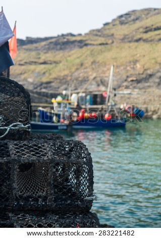 Rope and wooden frame lobster pot or trap stacked on stone wall of harbor in Boscastle, Cornwall, England UK - stock photo