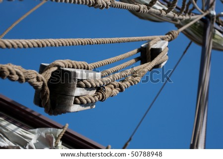 Rope hanging from a hook on sailboat railing. - stock photo
