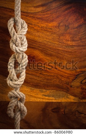 Rope knot on a teak wood background - stock photo