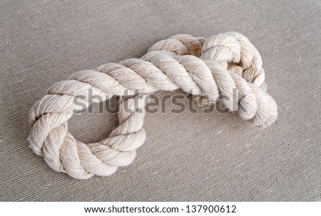Rope on a burlap background - stock photo