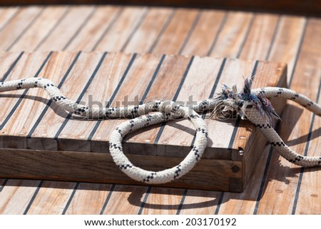 Rope on a wooden boat deck. Horizontal shot with copy space - stock photo