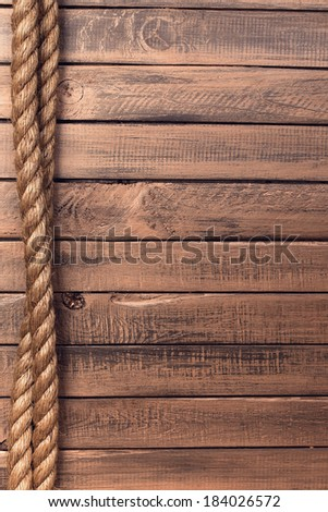 Rope on old wooden board background - stock photo