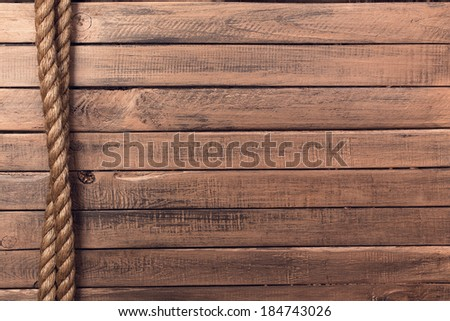 Rope on old wooden board background vertical - stock photo