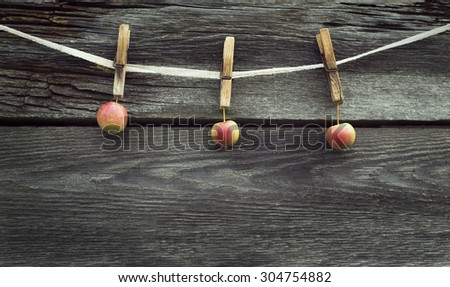 rope with clothespins and apples against old wood background with space for text on the bottom, topic of  harvest time - stock photo