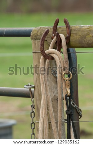 Ropes and chains hanging on a fence at a horse farm with horse shoes being used as hooks holding the ropes. - stock photo