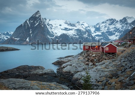 Rorbu cottages with Olstin mountain peak in background, Hamnoy village, Moskenesoy island, Lofoten Islands, Norway - stock photo