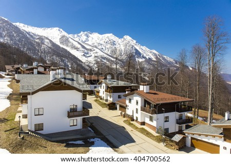 ROSA KHUTOR, RUSSIA - APRIL 01, 2016: Mountain ski resort Rosa Khutor and cottages on snowy mountains background