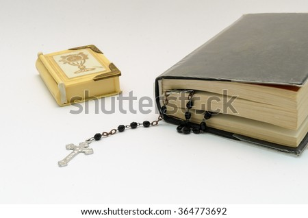 rosary beads in bible book and box for rosary on white background - stock photo