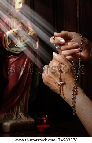 Rosary beads, light rays falling on hands - stock photo