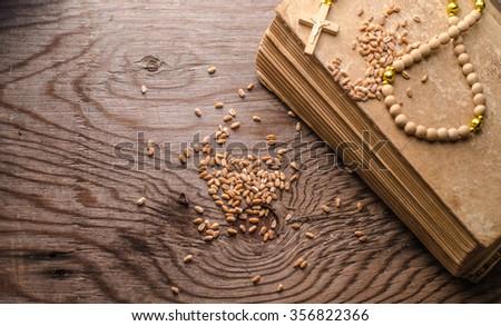 rosary beads on a vintage old books,grain wheat,horizontal photo - stock photo