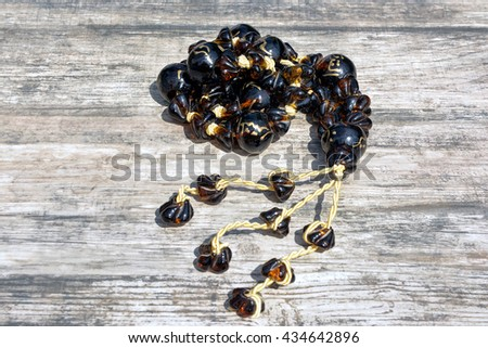 Rosary beads on wooden background - stock photo