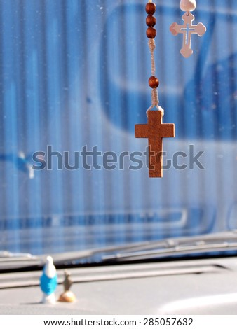 Rosary hang in car front window on rear view mirror      - stock photo