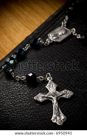 Rosary laying on bible - stock photo