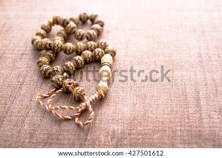 Rosary on wooden background - stock photo