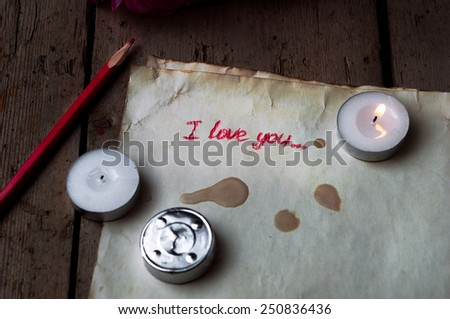 "Rose and a note with the text ""I love you"" on a wooden background.Spilled wax from a dead candle. - stock photo"