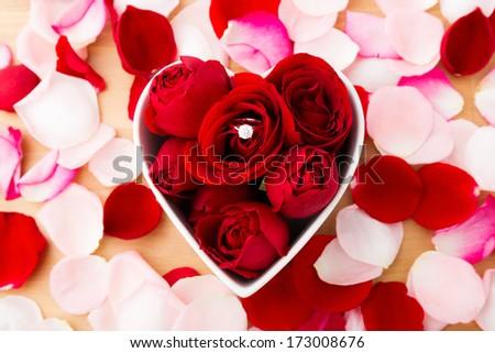 Rose and diamond ring inside the heart shape bowl - stock photo
