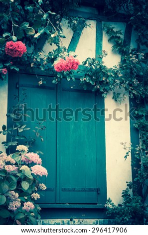 Rose and hydrangea bushes overgrowing half timbered house. French countryside. Toned photo. A game of light and shadow. - stock photo