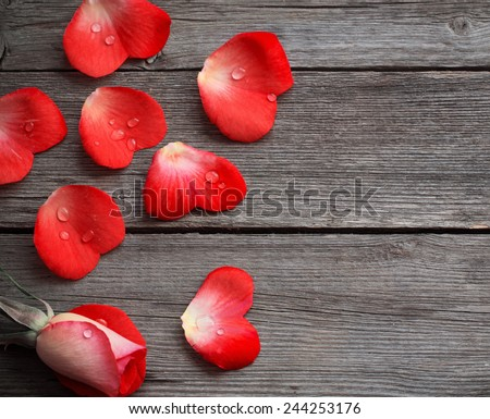 rose and petal in form heart on wooden background - stock photo