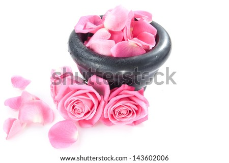 rose and rose petals in vessel over white