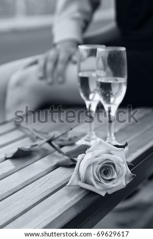Rose and two wineglasses with champagne on the bench in black and white with soft blue tint - stock photo