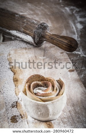Rose apples and dough. Homemade cakes on a light wooden table with flour. Toned. - stock photo