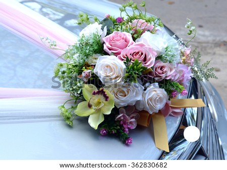 Rose artificial flowers bouquet on the bonnet car - wedding ceremony