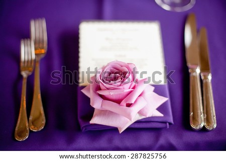 Rose at a formal dinner against a purple table cloth - stock photo